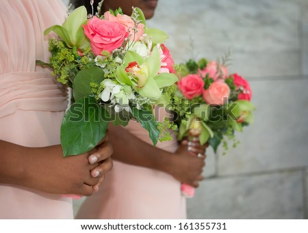 Wedding bouquets in hands of African American bridesmaids at ceremony - stock photo
