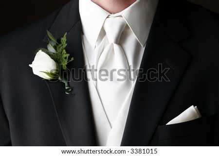 Wedding boutonniere pinned on the collar of a black wedding suit with white tie and handkerchief in pocket - stock photo