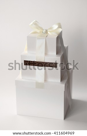Wedding box for money. Box in the form of a cake, decorated with ribbon. - stock photo