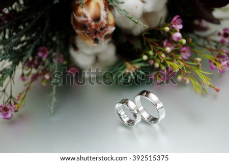 Wedding bridal bouquet wedding floristry and decor beautiful engagement ring in white gold with engraving platinum wedding rings near bouquet chic beautiful floral arrangement - stock photo