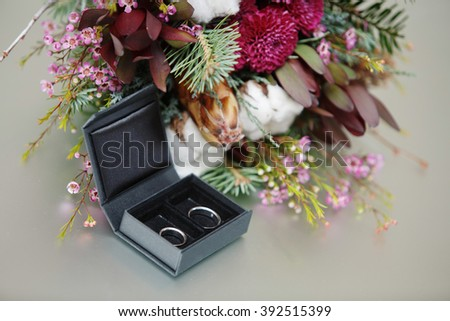 Wedding bridal bouquet Wedding rings in a black box beautiful engagement ring in white gold with engraving platinum wedding rings near bouquet chic beautiful floral arrangement - stock photo