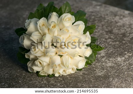Wedding bridal bouquet with gentle white roses on gray stone