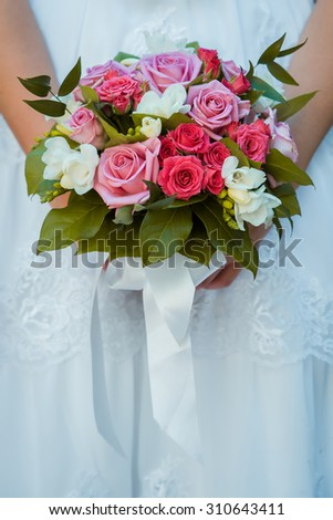 Wedding Bridal bouquet with pink and red roses in his hands - stock photo