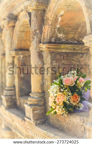 wedding bridal bouquet with white, peach and orange roses lies in the ancient building. Wedding theme - stock photo