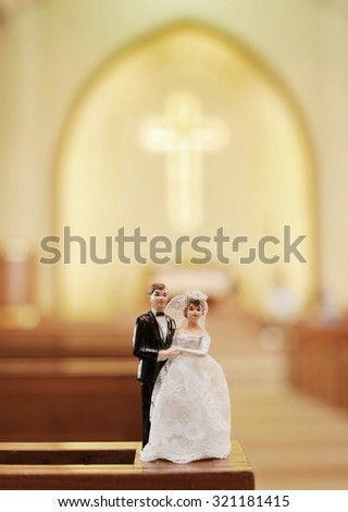wedding bride and groom couple doll in church with blur background cross - stock photo