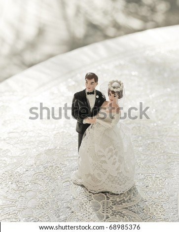 wedding bride and groom couple doll on lace table - stock photo