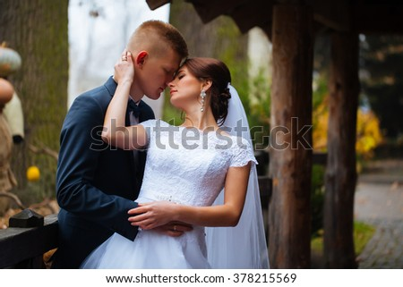 Wedding bride and groom kissing loving couple with roses bouquet flowers at winter bridal day Enjoy moment of happiness and having fun. playful newlywed family woman and man in love. gorgeous bride - stock photo