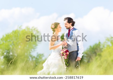 Wedding bride and groom toasting with sparkling wine outside on field