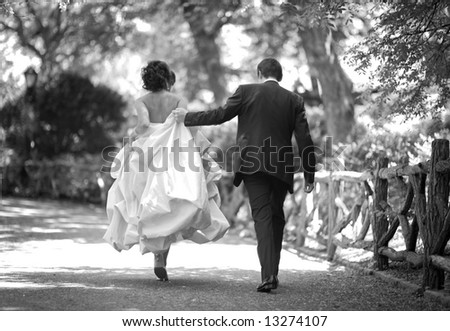wedding - bride and groom walking in the park - stock photo