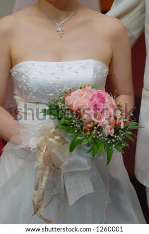 Wedding bride holding bouquet - stock photo