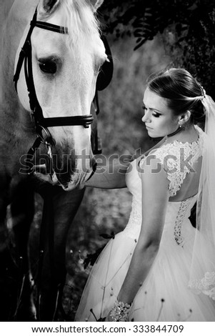 Wedding. Bride with white horse. Black and white image