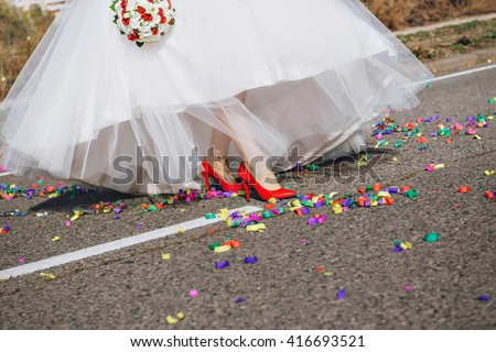 Wedding, bride woman leg in red shoes walking at confetti - stock photo