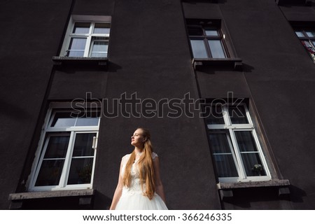 Wedding. Bright spot. Low angle portrait of a young woman in a wedding dress standing near a dark house smiling in the sunlight - stock photo