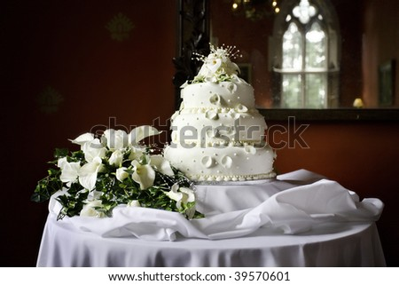 wedding cake and bouquet against a red wall