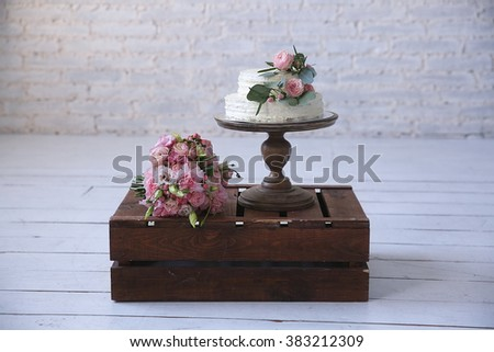 wedding cake and flowers on wooden box on the floor - stock photo