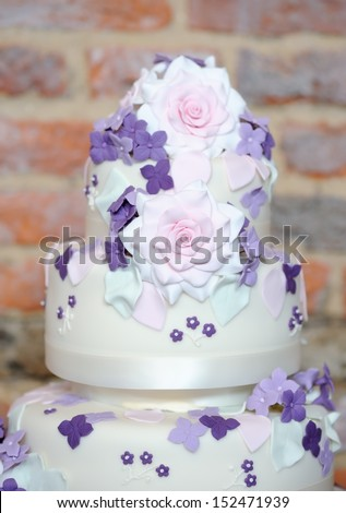 Wedding cake closeup showing pink and purple floral details - stock photo