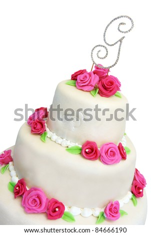 Wedding cake covered in ivory marzipan and decorated with pink roses - stock photo