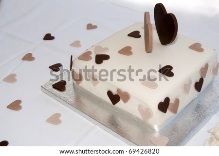 Wedding cake decorated with brown hearts - stock photo