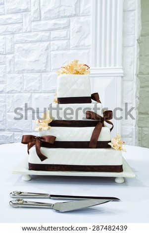 Wedding cake, decorated with brown ribbon and yellow flowers - stock photo
