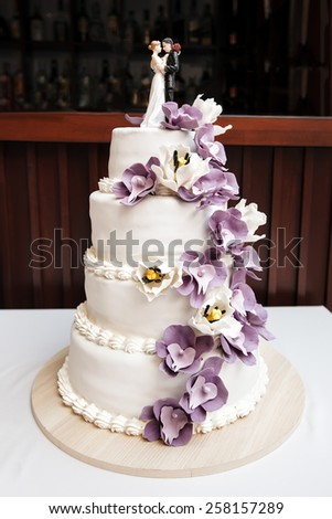 Wedding cake, decorated with purple flowers and figurines of bride and groom - stock photo