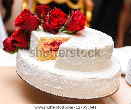 Wedding cake decorated with red roses - stock photo