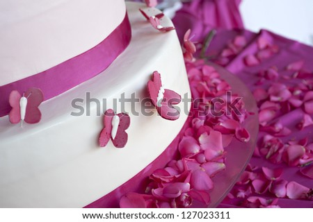wedding cake decorated with rose petals and butterflies - stock photo