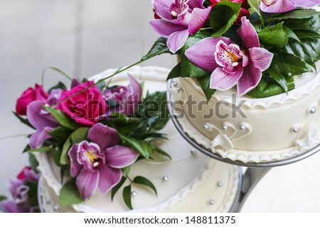 Wedding cake decorated with stunning purple and pink orchids - stock photo