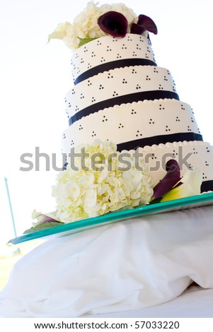 Wedding cake detail at a marriage ceremony and reception. The cake is white with black and has flowers on it and frosting. - stock photo