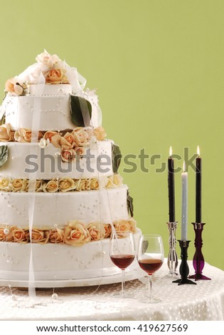 wedding cake green wall and candle with red wine - stock photo