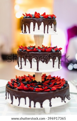 wedding cake in chocolate with strawberries and blueberries  - stock photo