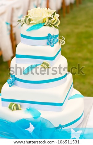 Wedding cake in white and blue combination, adorned with flowers, ribbons and butterflies - stock photo