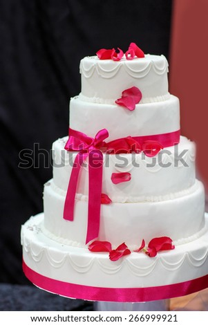 Wedding cake in white and pink decorated with flowers.