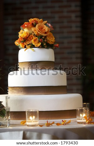 wedding cake lit bright from the side, reddish orange flowers. Out of focus candles in the foreground, focus on the cake and flowers. A dark background that could be separated from the cake - stock photo