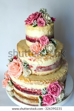 Wedding cake. Naked handmade cake rustic, decorated with roses. - stock photo