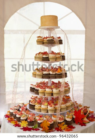 Wedding cake of cupcakes with autumn leaves at reception - stock photo