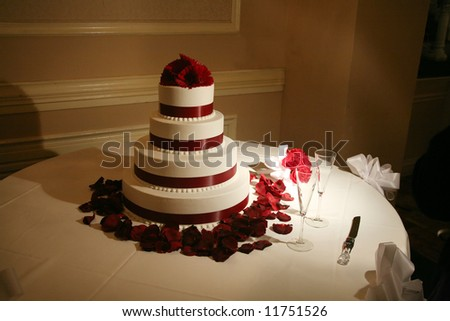 Wedding cake under low romantic light with petals around it - stock photo
