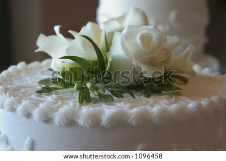 Wedding cake with a white rose on top - stock photo