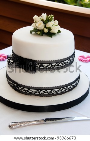 Wedding cake with black lace ribbon and white icing and little pink hearts and knife - stock photo