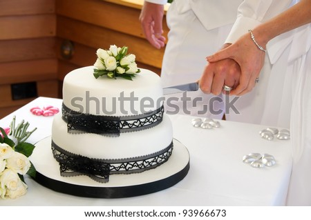 Wedding cake with black lace ribbon and white icing and little pink hearts and knife with bride and groom cutting - stock photo