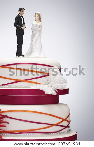 Wedding Cake with Bride and Groom Figurines - stock photo