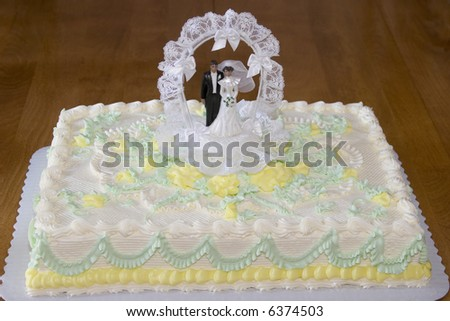 Wedding cake with bride and groom on wooden table - stock photo