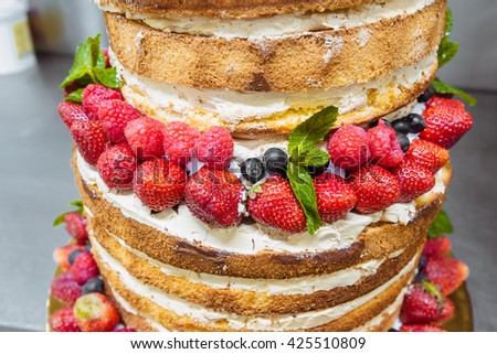 wedding cake with open biscuit shortcakes, cream and fruit. blueberries, strawberries, raspberries, red currants. cake stands on the work surface. - stock photo