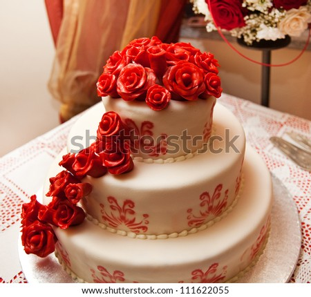 Wedding cake with red roses - stock photo