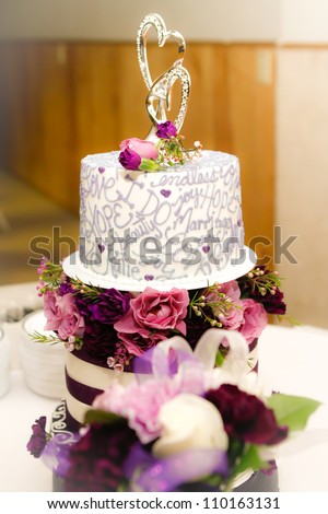 Wedding cake with silver heart topper and purple flowers - stock photo