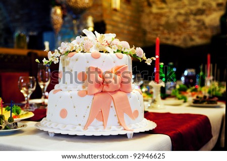 Wedding cake with white icing and pink bow - stock photo