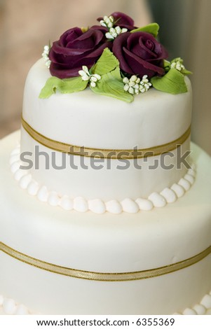 Wedding cake with white icing decorated with marzipan roses - stock photo