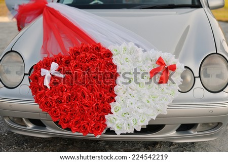 Wedding car decorated with two hearts made �¢??�¢??of flowers. - stock photo