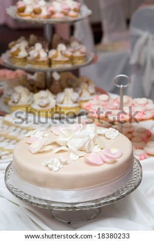 Wedding celebration with pink cake and icing decorated with rose petals - stock photo