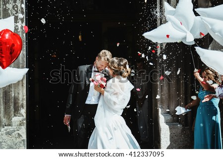 Wedding ceremony. Bride and groom embracing near church  and smiling. A lot of flowers, confetti and balloons. Guests around. Outdoor - stock photo