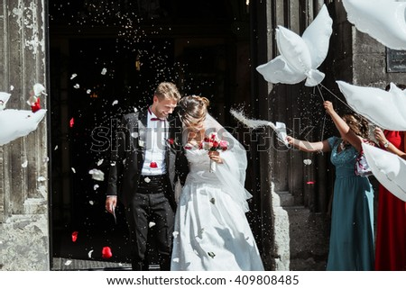 Wedding ceremony. Bride and groom going out of church holding each other with one had and smiling. A lot of flowers, confetti and balloons. Outdoor - stock photo